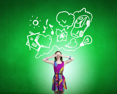 eyes closing: Young girl in multicolored dress closing eyes with palms Stock Photo