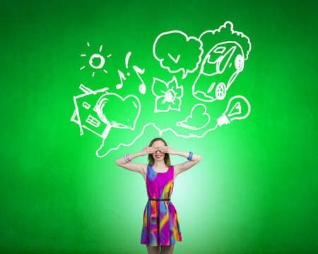 closing eyes: Young girl in multicolored dress closing eyes with palms Stock Photo