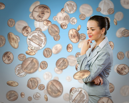corporate greed: Image of thoughtful businesswoman standing under coin rain Stock Photo