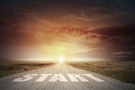 horison: Start word on asphalt road and sunrise at horison line Stock Photo