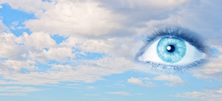heaven light: Female clear eye on blue sky background Stock Photo