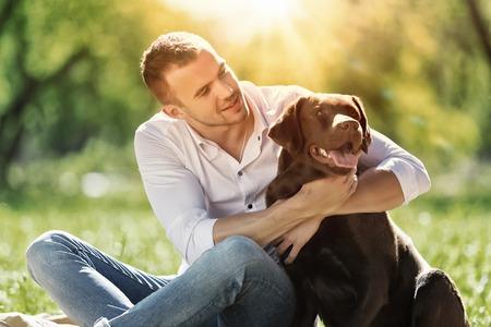 dog days: El individuo joven con el perro perdiguero de paseo en el parque de verano