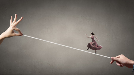 blindfold: Woman in evening dress and blindfold walking on rope Stock Photo