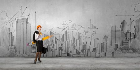 woman engineer: Woman engineer with huge pencil and construction sketches at background
