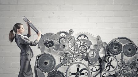 inteligencia: Joven empresaria mecanismo de fijaci�n de los engranajes con la llave