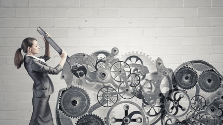 intelligence: Young businesswoman fixing gears mechanism with wrench