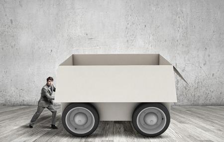 young businessman: Young businessman pushing carton box on wheels