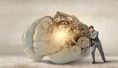 solver: Young businessman leaning on big brain model