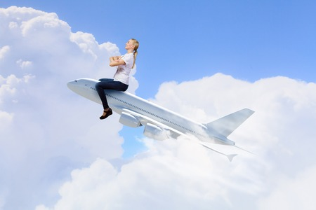 atop: Young woman riding drawn airplane flying in air