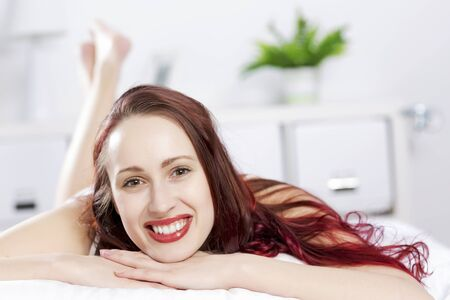 calm woman: Young happy woman lying in bed and smiling