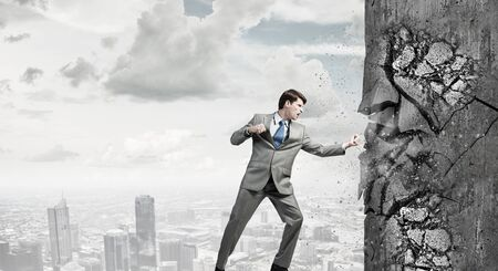 fedup: Businessman breaking stone wall with karate punch