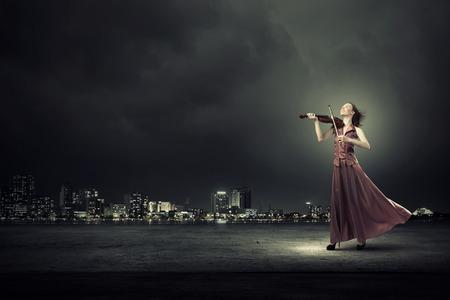 violines: Violinista femenino joven en vestido de noche largo