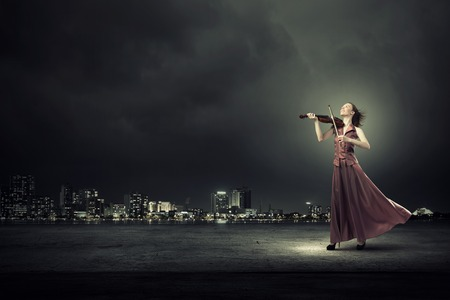 playing instrument: Young female violin player in long evening dress