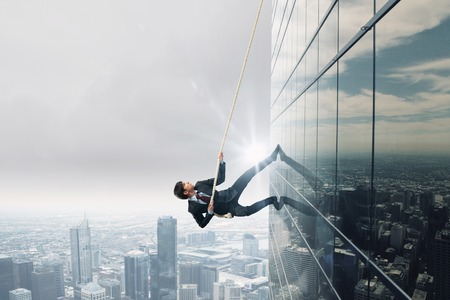 business activity: Concept of competition with businessman climbing office building with rope Stock Photo