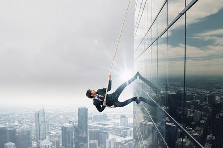 Concept van de concurrentie met zakenman klimmen kantoorgebouw met touw