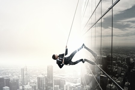 business success: Concept of competition with businessman climbing office building with rope Stock Photo