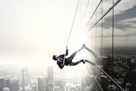 climber: Concept van de concurrentie met zakenman klimmen kantoorgebouw met touw