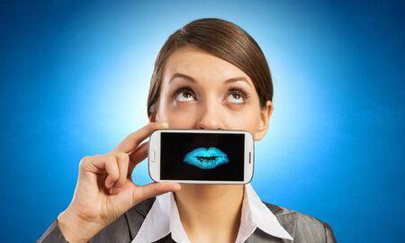boca: Joven y bella mujer que sostiene el tel�fono m�vil contra su boca y sonriendo