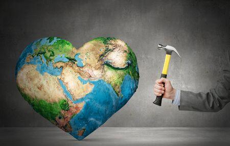 demografia: Cierre de martillo en la mano del hombre que golpea el planeta Tierra. Elementos de esta imagen son proporcionados por la NASA Foto de archivo