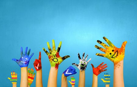 bright colors: Image of human hands in colorful paint with smiles Stock Photo
