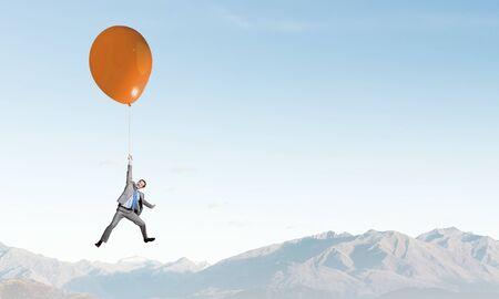 mosca: Joven empresario de éxito vuela en globo colorido