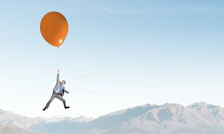 flies: Young successful businessman flies on colorful balloon