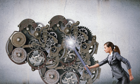 power wrench: Young businesswoman fixing gears mechanism with wrench