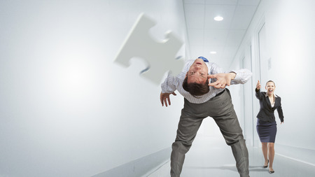 bent over: Businessman bent over and evading from flying puzzle element