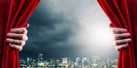 curtain: Close up of hand opening red curtain. Place for text Stock Photo