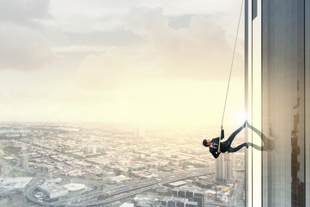 Concept of competition with businessman climbing office building with rope Stock Photo