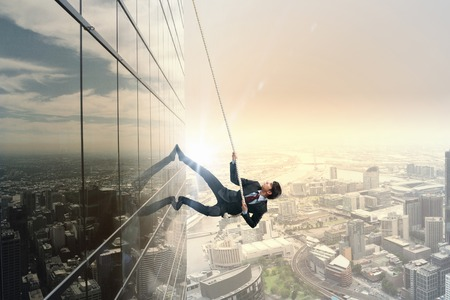 Concept of competition with businessman climbing office building with rope Reklamní fotografie