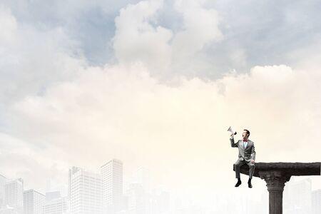 megafono: Hombre de negocios sentado en el borde de la roca y gritando en el meg�fono Foto de archivo