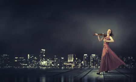 soloist: Young female violin player in long evening dress