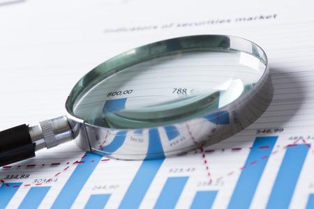 Magnifing Glas und Dokumente mit Analytics-Daten liegen auf dem Tisch Standard-Bild - 42343798