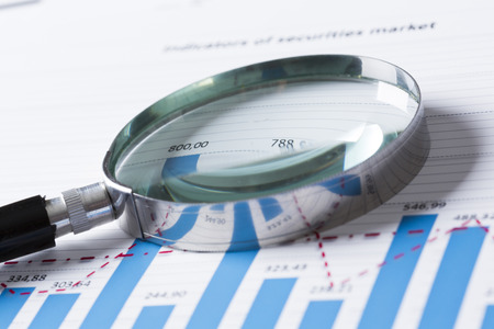 survey: Magnifing glass and documents with analytics data lying on table