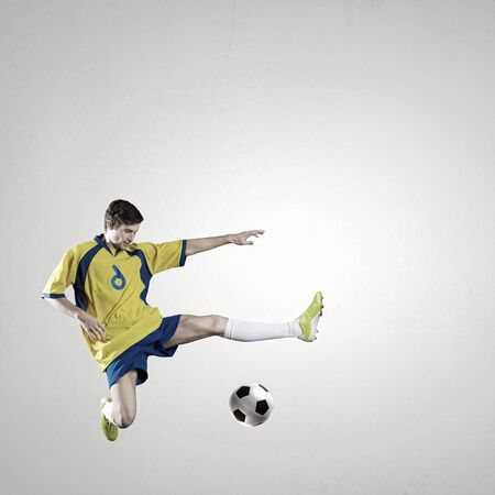 kicking ball: Soccer player kicking ball isolated over white background