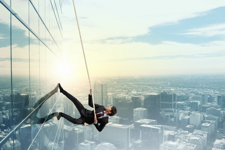 Concept of competition with businessman climbing office building with rope Foto de archivo