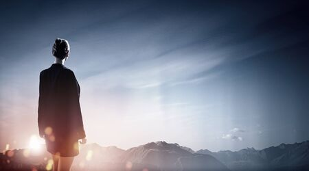 away: Back view of businesswoman against mountain landscape looking far away