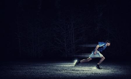 corriendo: Hombre corriente en ropa de deporte azul sobre fondo negro