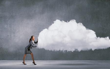 empujando: Empresaria atractiva empujando gran nube con un esfuerzo Foto de archivo