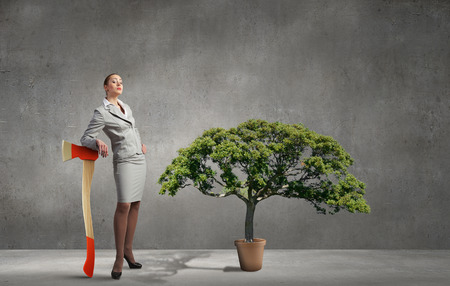 deforestation: Businesswoman with axe representing problem of deforestation