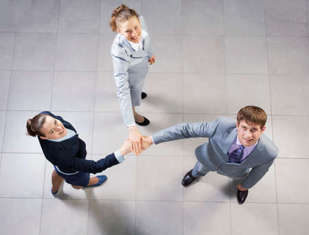 uniting: Top view of business people uniting hands in pile Stock Photo