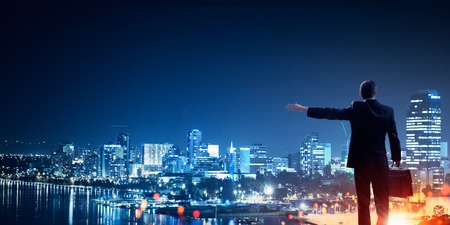 lawer: Rear view of businessman against night city gesturing with hand