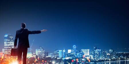 gesturing: Rear view of businessman against night city gesturing with hand