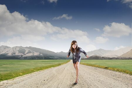 start position: Young determined businesswoman standing in start position