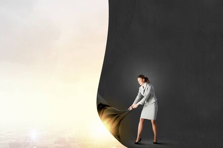 business change: Young pretty businesswoman pulling clothing blank banner Stock Photo