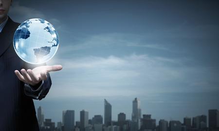 デジタル地球を示す実業家の手のクローズ アップ