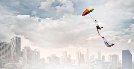confident woman: Business people flying in the sky on umbrella Stock Photo