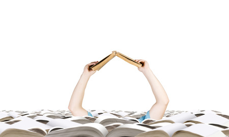 reaching out: Hand with book reaching out from pile of old books Stock Photo