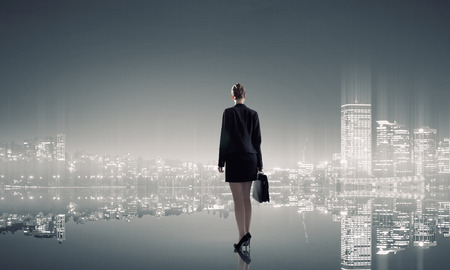 leader: Businesswoman standing with back against night city panoramic view